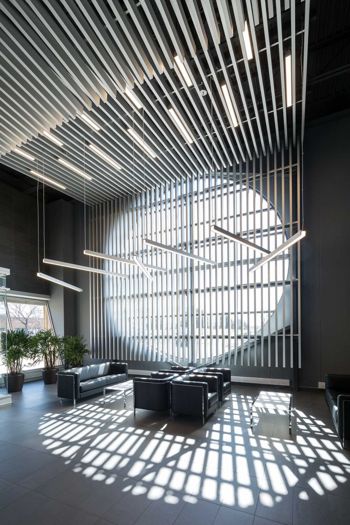 A slat screen of aluminum, the metal perhaps most often associated with aerodynamics, wraps the walls and ceiling above the desk and seating areas. The slats' anodized finish and finger joints impart high-tech sleekness to the lobby.